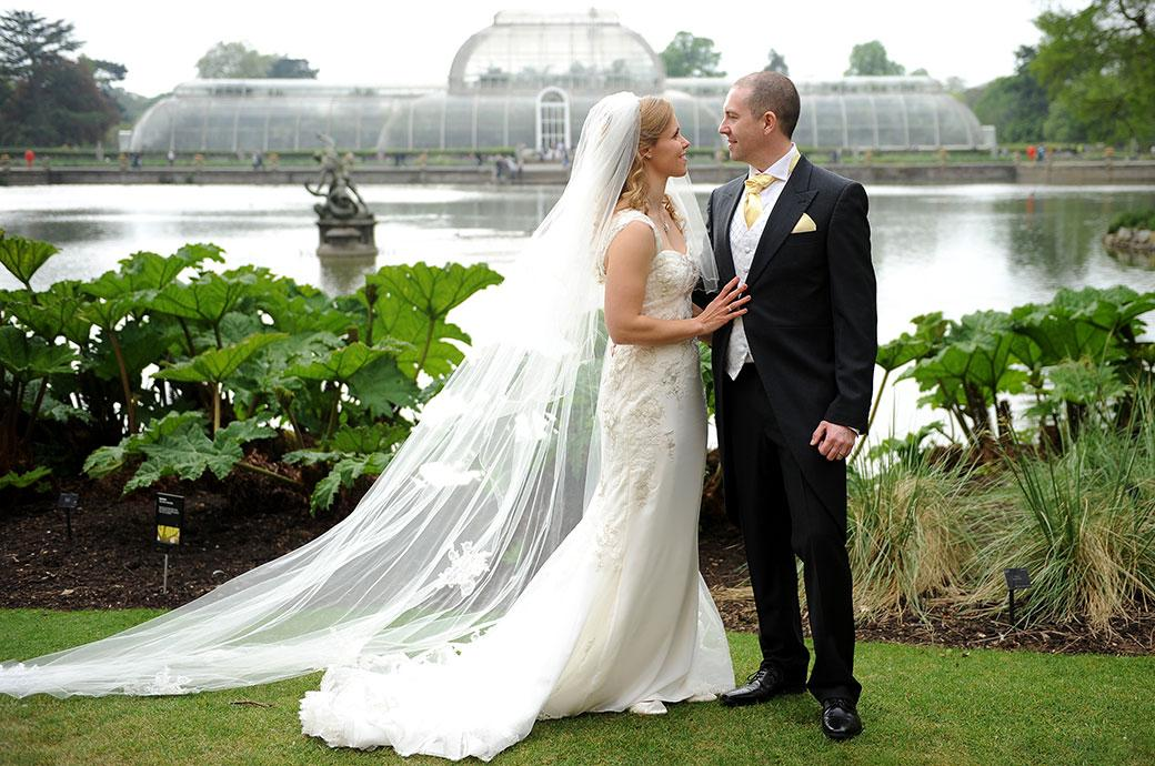 Classic wedding photograph from world famous Surrey wedding venue Kew Gardens of a Bride and groom standing before the pond  in front of the