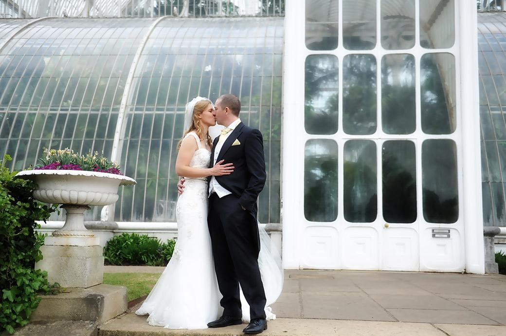 Romantic Bride and groom wedding photograph taken at the world famous Kew Gardens and Surrey wedding venue as they kiss outside the Palm House