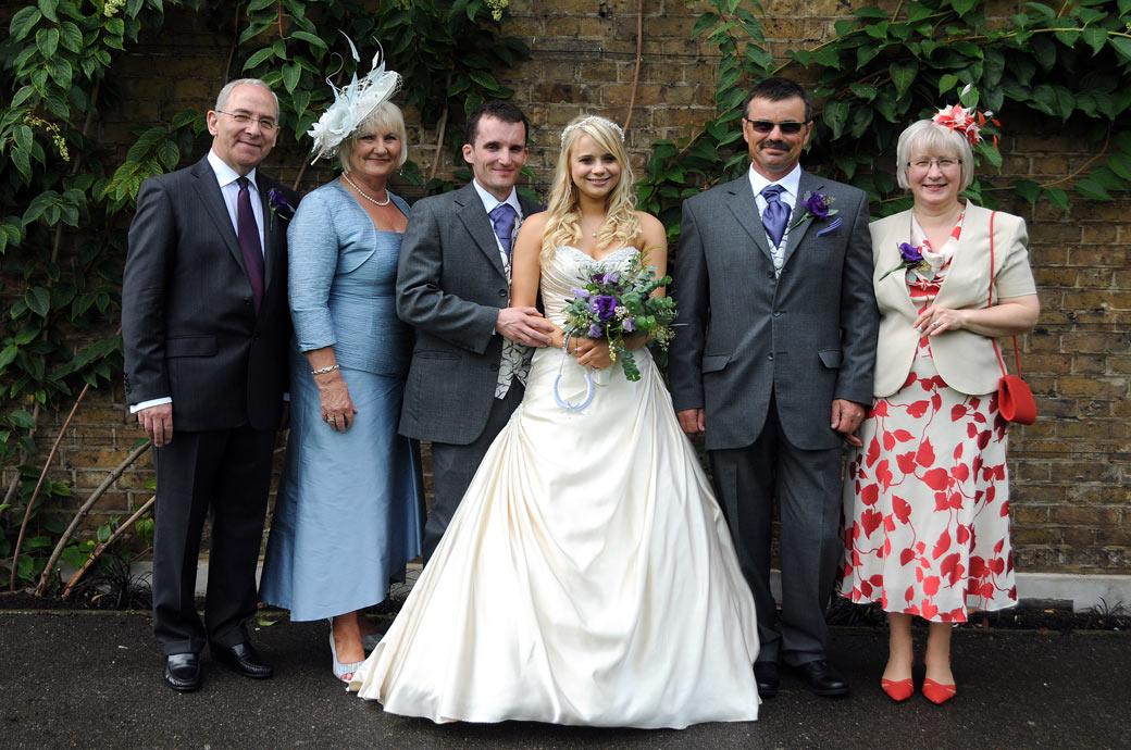 Newly-weds with parents in a group wedding photograph taken in the Duke's Garden at Cambridge Cottage Kew Gardens by Surrey Lane wedding photography