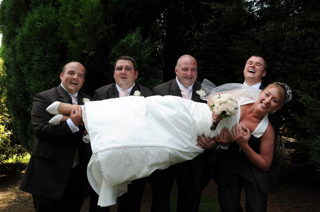 Bride enjoys the moment as the Groom and groomsmen pick her up for a wedding photo at Surrey wedding venue Kingswood Golf Club out on the lawn