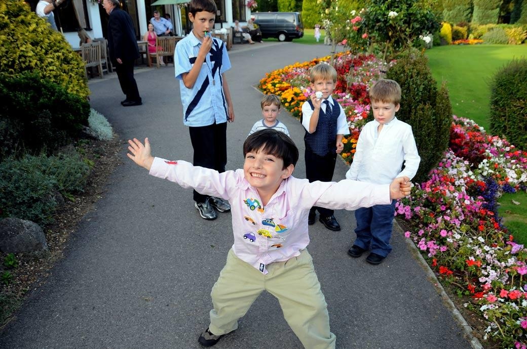A boy with lots of badges poses for the Surrey Lane wedding photographer in this fun wedding photo taken in Tadworth Surrey at Kingswood Golf Club on the colourful terrace