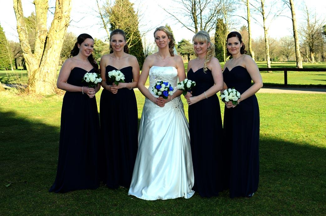 All smiles for the lovely Bride and her pretty bridesmaids in this relaxed wedding picture taken on the lawn at Kingswood Golf Club a popular wedding venue in Surrey