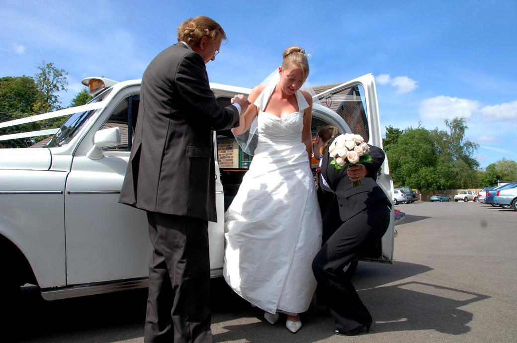 Bride being helped out of her white Hackney cab by her father in this wedding photo taken at Kingswood Golf Club by Surrey Lane wedding photographers
