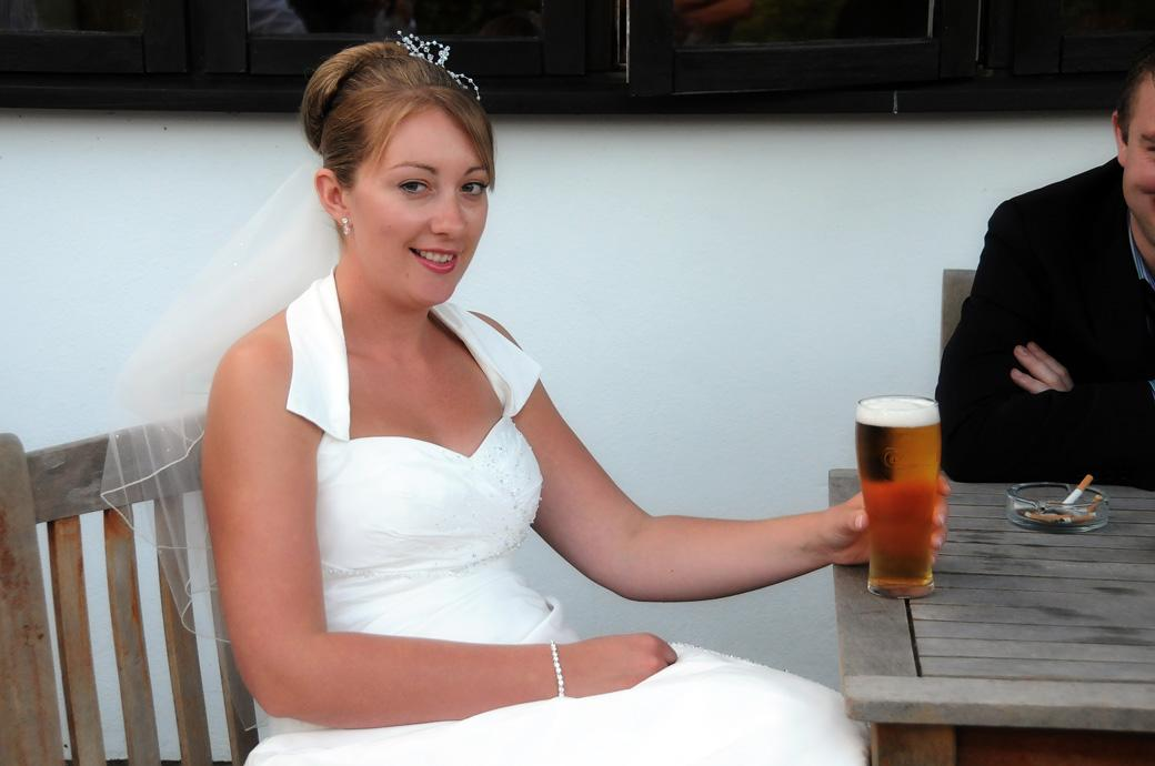 Bride takes a time to relax with a pint of cold lager in this humorous wedding photograph taken at Surrey wedding venue Kingswood Golf Club on The Terrace