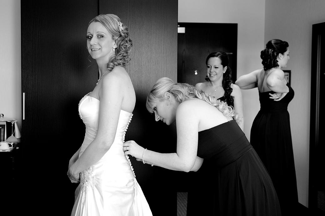 Smiling Bride looks over as a Bridesmaid finishes fastening her beautiful dress in this relaxed wedding photo taken in the Lodge at Surrey wedding venue Kingswood Golf Club