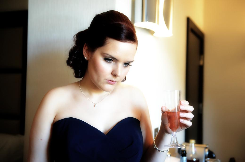 Bridesmaid with drink in hand watching the bride having her make-up completed captured by a Surrey Lane wedding photographer at Kingswood Golf Club in a suite at The Lodge