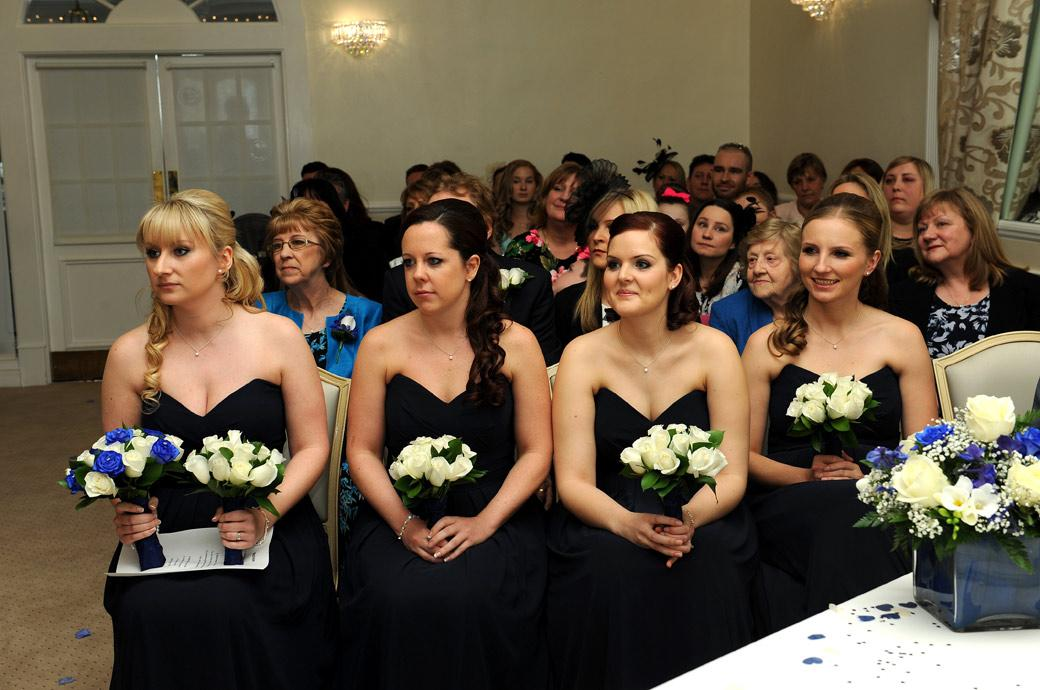 Bridesmaids sitting in the front row of the wedding ceremony in the Ballroom at Surrey wedding venue Kingswood Golf Club look on the affair with love and attention