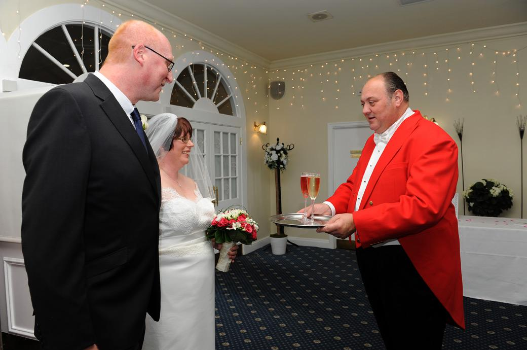 Happy newlyweds are presented with champagne from their toastmaster as they leave the wedding ceremony room at Kingswood Golf Club in Tadworth Surrey