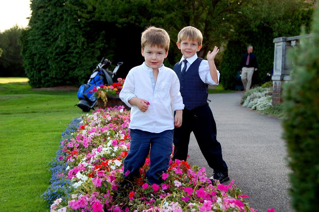 Children amongst the brightly coloured flower beds at a wedding reception captured by Surrey Lane wedding photographers out on the terrace at Kingswood Golf Club