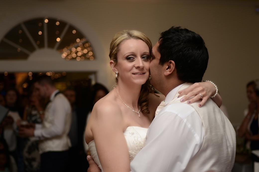 Bride smiles as she shares a moment with her husband as they enjoy their first dance in Surrey wedding venue Kingswood Golf Club in the Ballroom