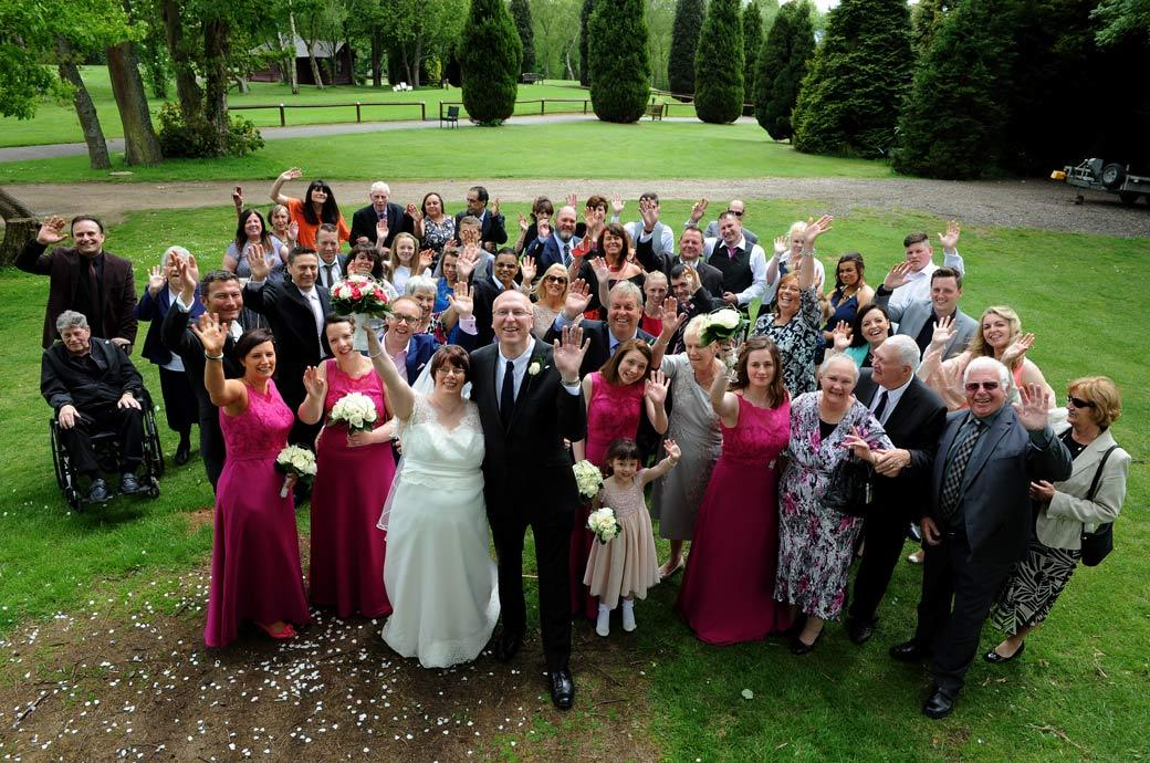 Everyone in this classic fun wedding photograph waving up at the Surrey Lane wedding photographer at Kingswood Golf Club from the top of the woodpile