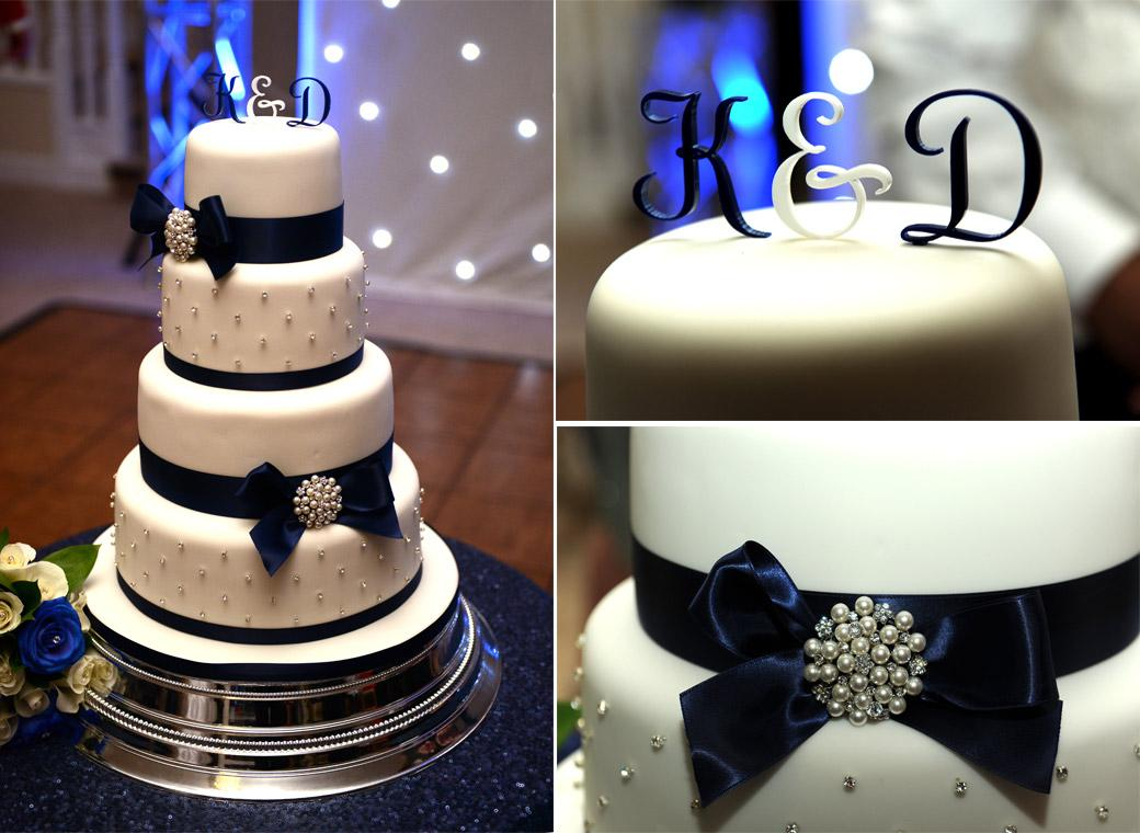 Four tiered wedding cake in blue white and silver awaiting the arrival of the Bride and Groom for the traditional cutting at Kingswood Golf Club a popular Surrey wedding venue