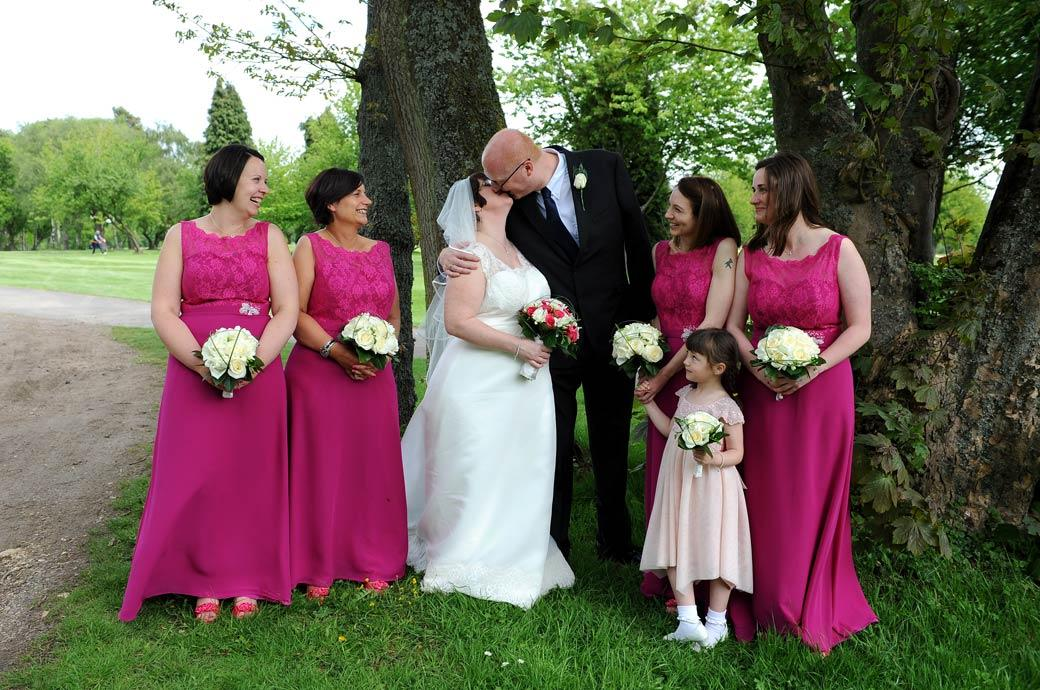 Groom kisses his Bride as the bemused Bridesmaids in pink look on in this funny group wedding picture taken on the lawn at Tadworth Surrey at Kingswood Golf Club
