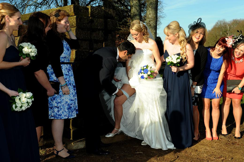 The groom locates his wife's garter to the amusement of the Bride and her accompanying ladies captured by a Surrey Lane wedding photographer at Kingswood Golf Club Tadworth