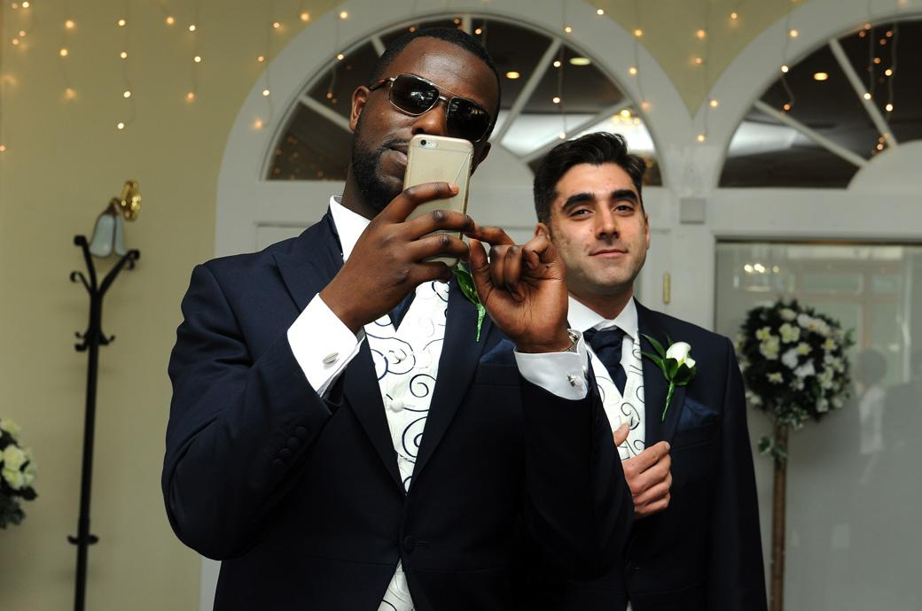 A sparkling wedding photograph of a Groomsman in Surrey lining up his camera phone for a classic Kingswood Golf Club shot on route to the marriage ceremony room