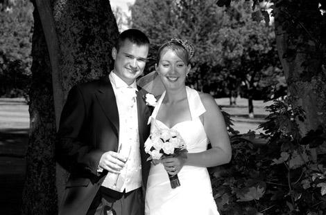 Happily married couple relaxing in the shade of the trees at Surrey wedding venue Kingswood Golf Club with wedding bouquet and celebratory glass of champagne in hand