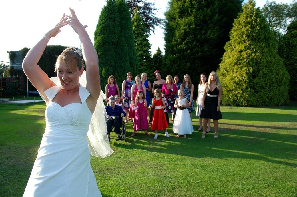 Fun wedding photo of the Bride throwing her bouquet to the awaiting ladies on the lawn at Surrey wedding venue Kingswood Golf Club