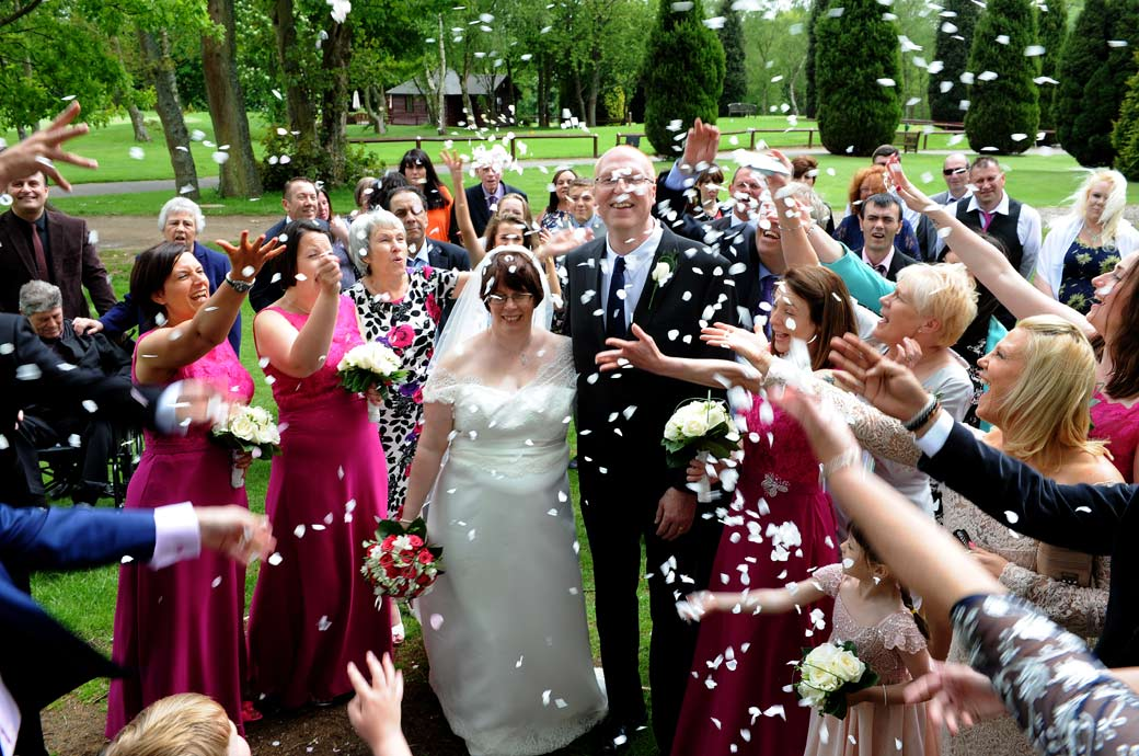 Confetti fun time for the newlyweds as all the guests shower them with confetti in this wedding photo captured at Kingswood Golf Club by Surrey Lane wedding photographers