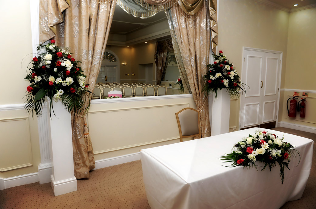 The wedding ceremony table with beautiful bouquets and empty seats reflected in the mirror captured in this wedding picture taken in Surrey in the Kingswood Golf Club Ballroom