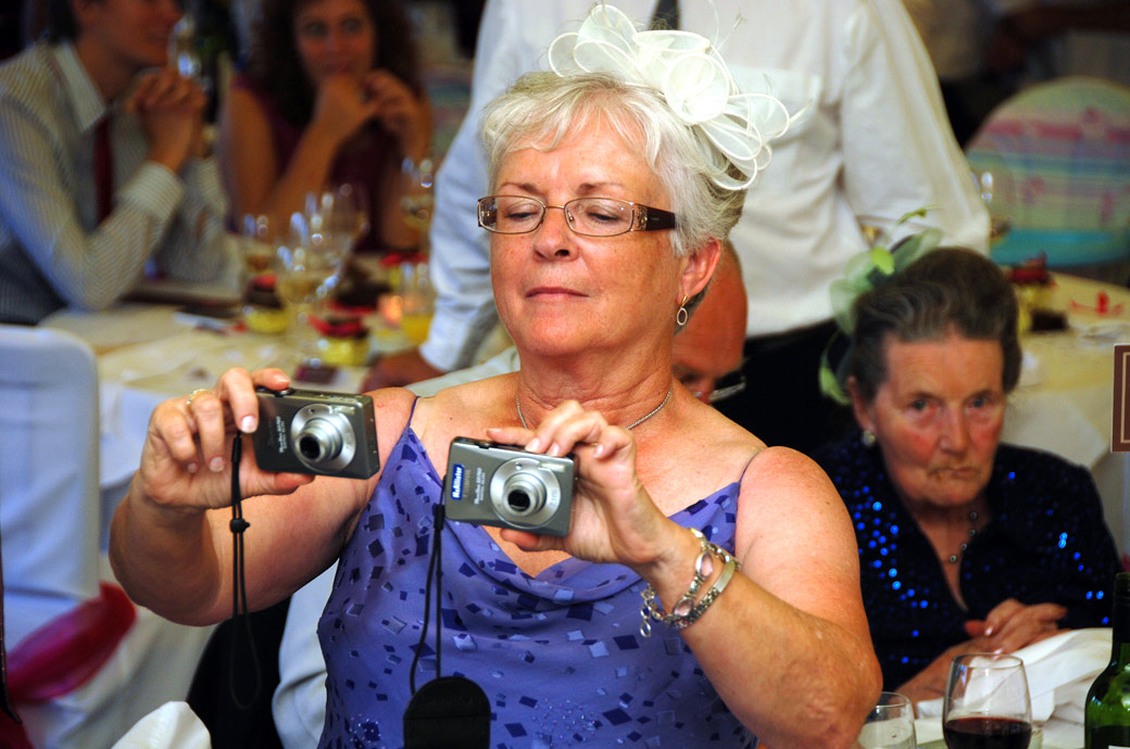 Lady takes pictures of the wedding cake with two camera's in this fun wedding photo taken in The Conservatory at Kingswood Golf Club in Tadworth Surrey