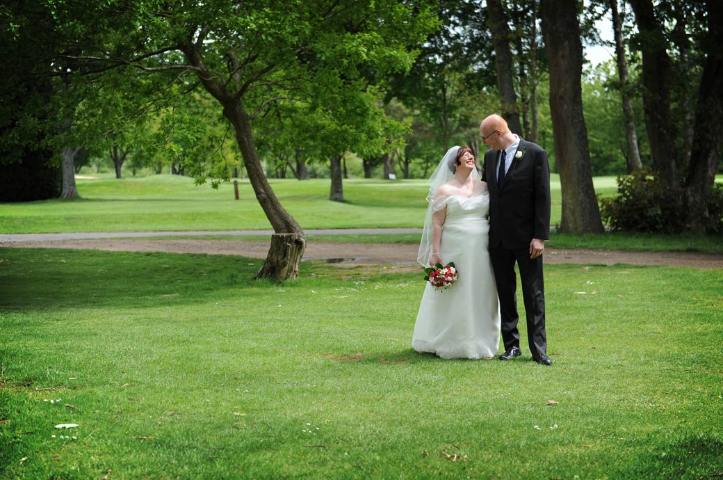 Romantic loving look on the lawn by the happy newlywed couple as they take time out from the wedding for time together at Kingswood Golf Club in the Surrey countryside