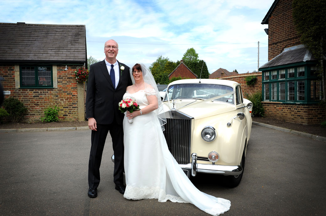 Smiling Bride and Groom in Tadworth Surrey standing proud in front of their cream Rolls Royce wedding car at the entrance to Kingswood Golf Club