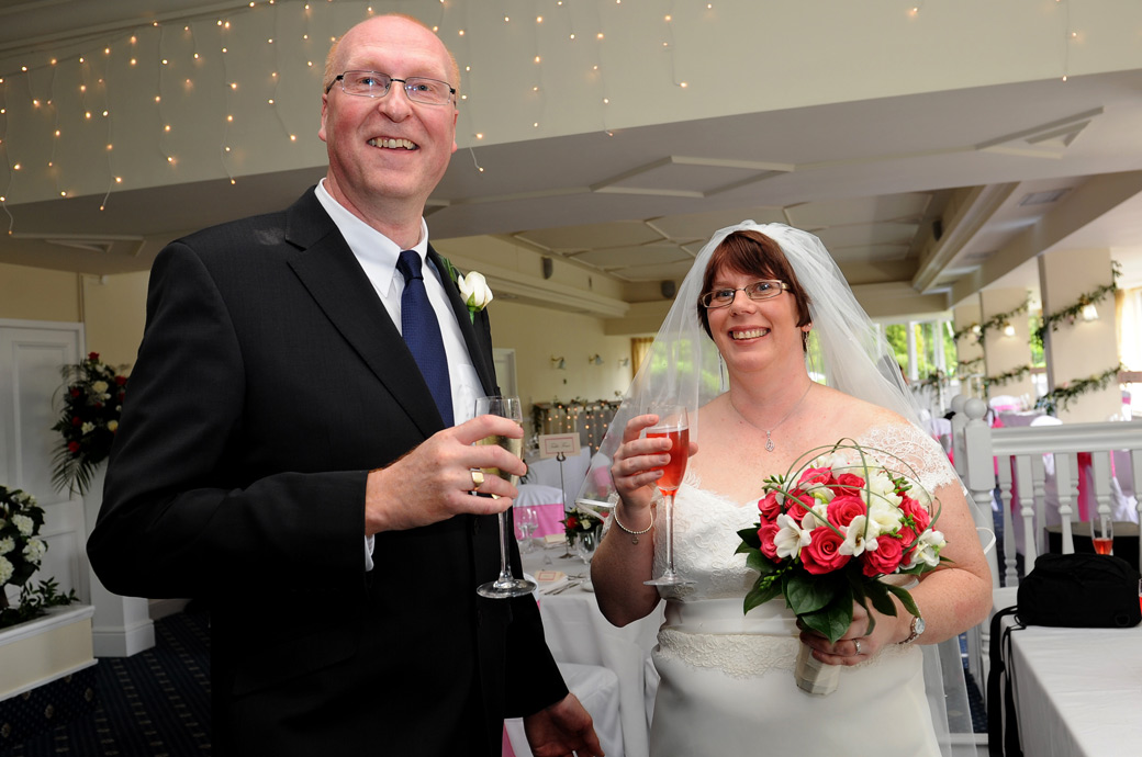 Beaming Bride and Groom celebrate with a champagne toast after getting married in the Ballroom ceremony room at Surrey venue Kingswood Golf Club in Tadworth