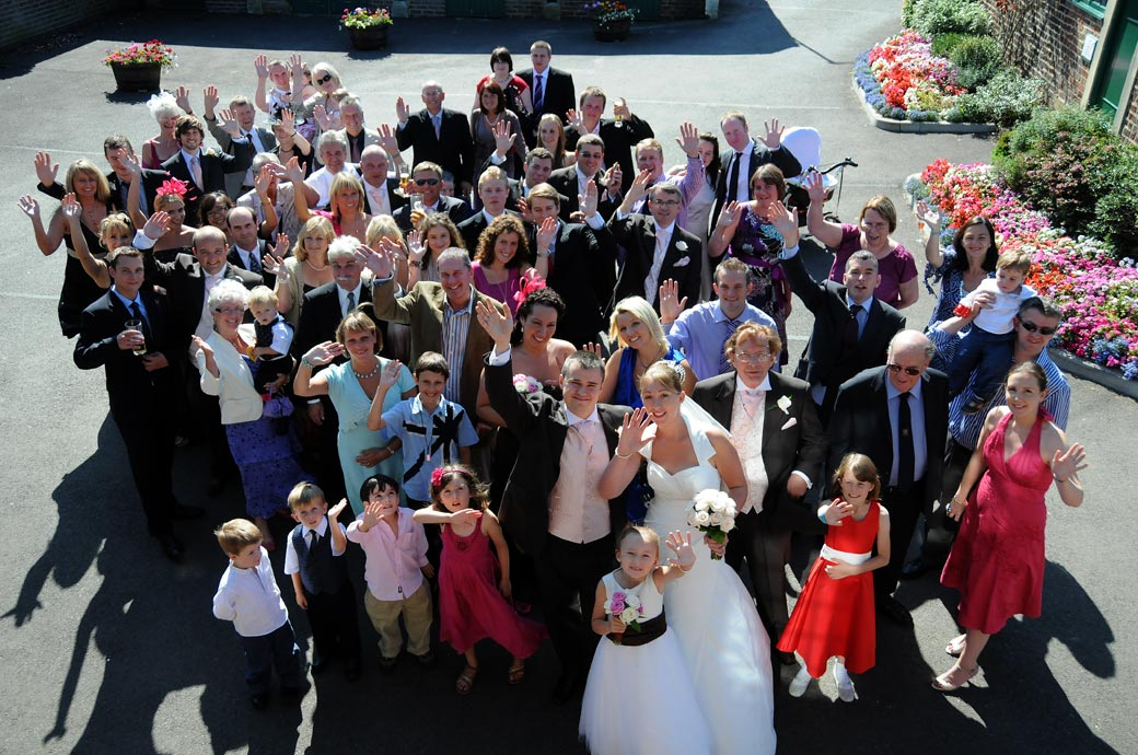 Guests standing on the sunny terrace waving for the everyone wedding picture taken at the popular Surrey wedding venue in Tadworth Kingswood Golf Club