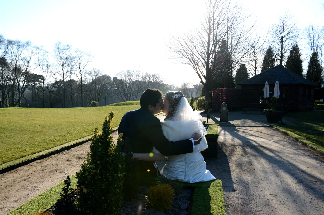 A lovely romantic wedding photograph taken from the back of a married couple sitting down and kissing  in the relaxing grounds of Kingswood Golf Club Surrey