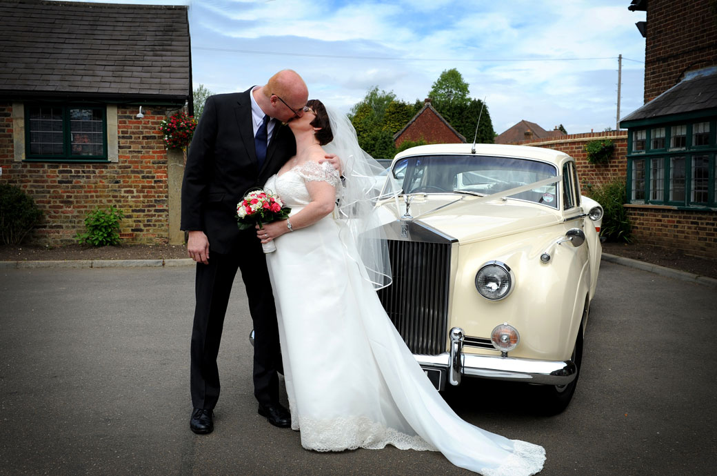 Bride and groom have a romantic kiss in front of their cream Rolls Royce wedding car outside Kingswood Golf Club captured by a Surrey Lane wedding photographer