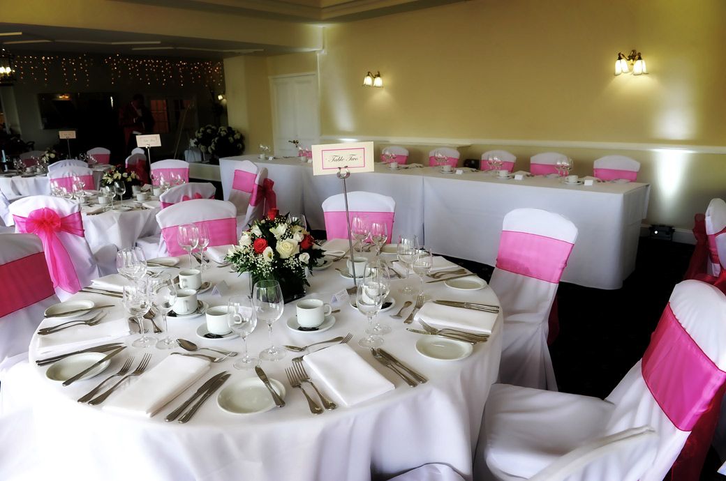 A wedding photograph of The Conservatory at Surrey wedding venue Kingswood Golf Club dressed in pink for the wedding breakfast and awaiting the arrival of the guests