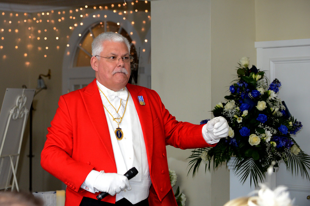 Toastmaster calls for silence as he announces the start of the wedding speeches in The Conservatory at Kingswood Golf Club a popular wedding venue in Tadworth Surrey