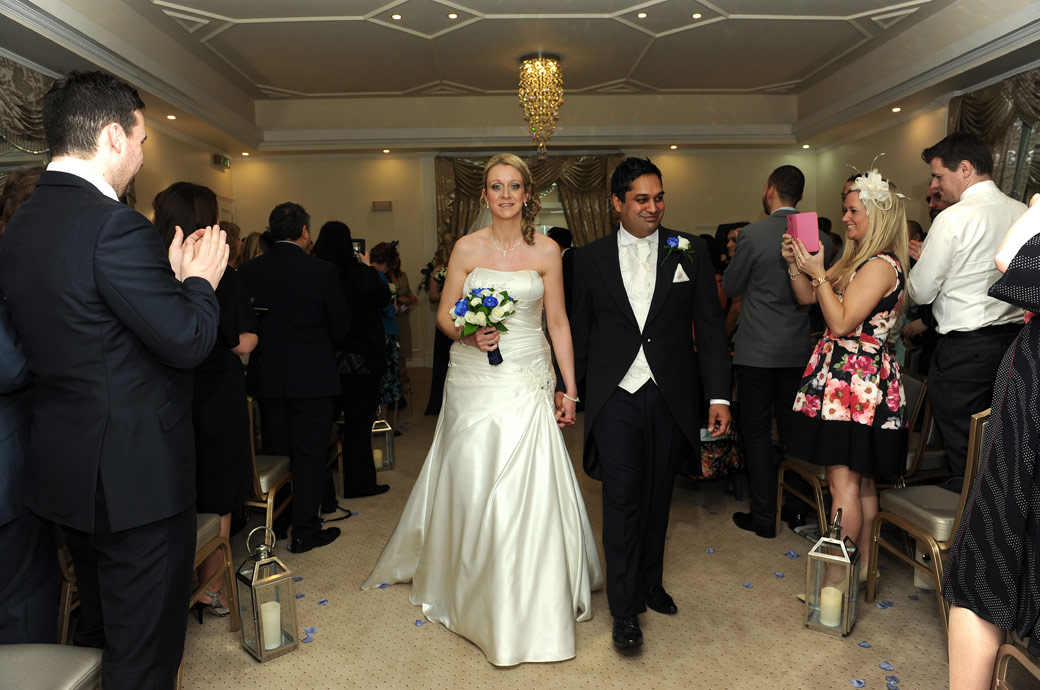 Happy and emotional couple walk down the aisle of the Ballroom past the applauding wedding guests at Kingswood Golf Club Tadworth in Surrey as husband and wife