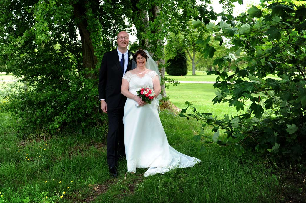 Happy smiling newlywed couple standing relaxed and content below some trees in the lovely tranquil grounds of Kingswood Golf Club in Surrey