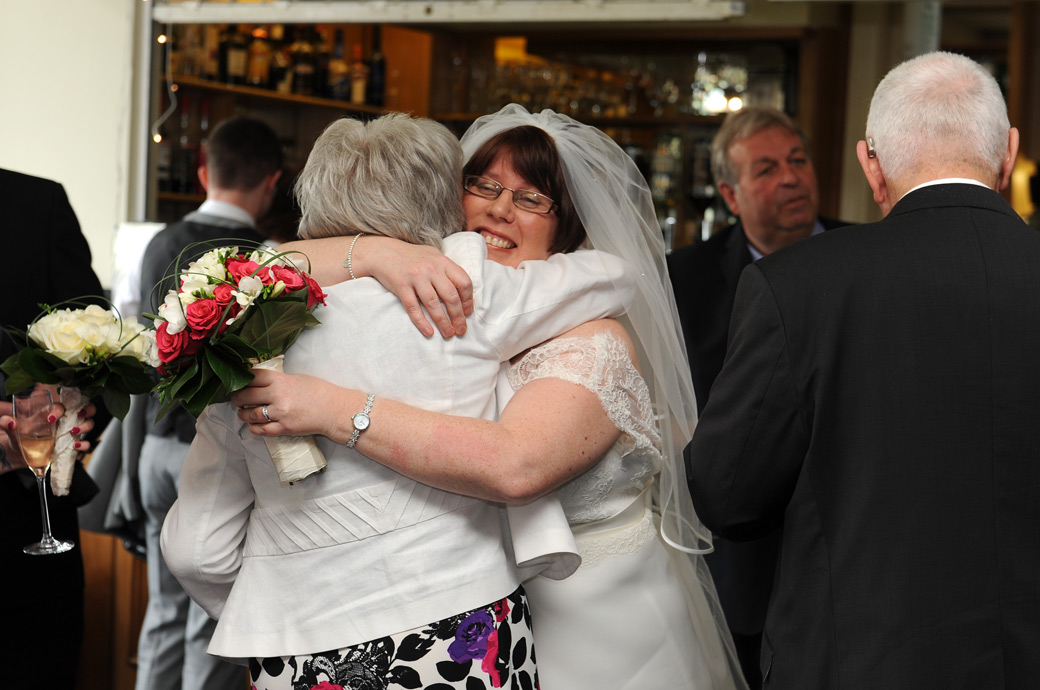 A hug of joy for the delighted Bride as she celebrates getting married at Kingswood Golf Club in Tadworth caught by Surrey Lane wedding photographers