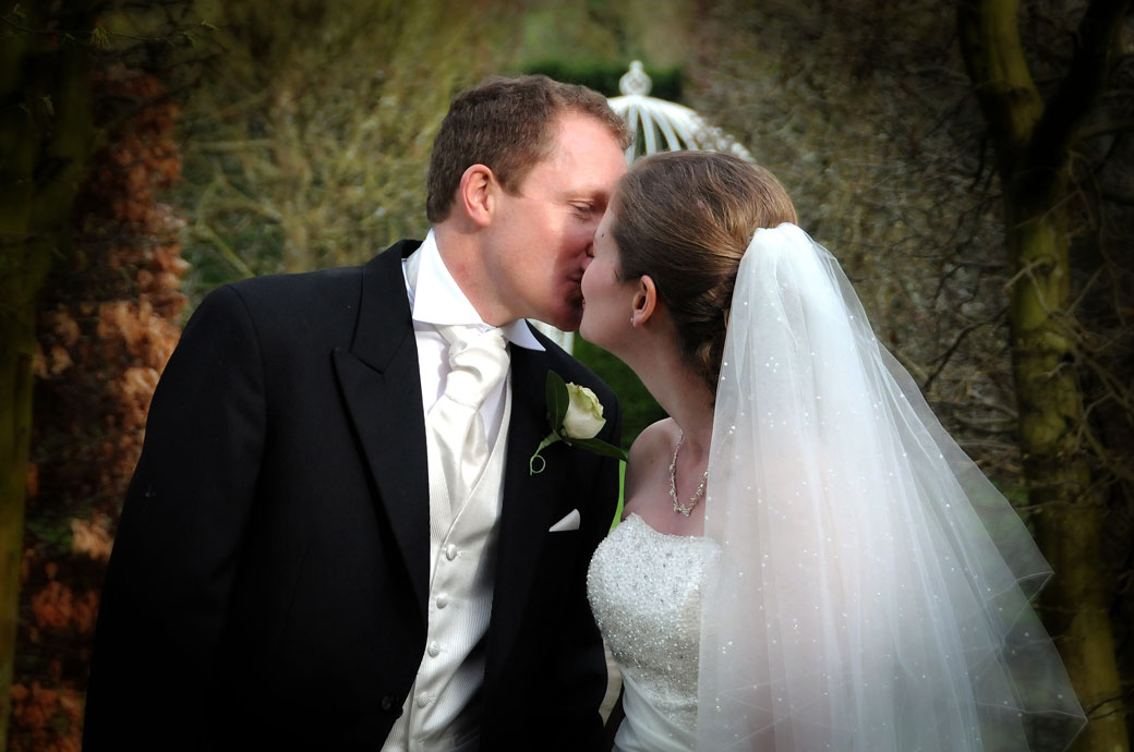 A stolen kiss romantic moment captured in this discreet wedding photograph at the Surrey wedding venue  Langshot Manor