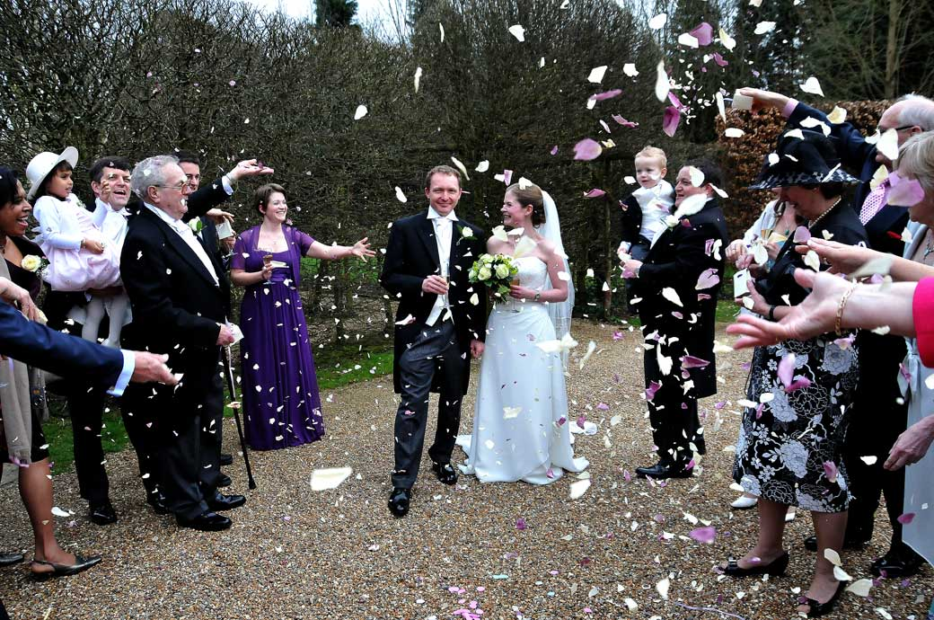Bride and Groom in a flurry of confetti wedding photograph captured on the drive outside the 16th Century Langshot Manor Surrey wedding venue