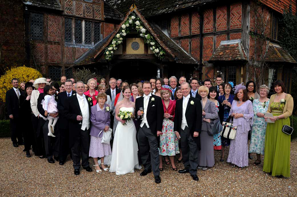 An everyone group wedding photograph taken at the front of the elegant 16th Century timber framed Surrey wedding venue Langshot Manor