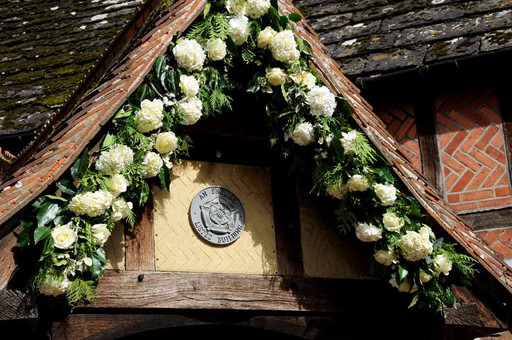 A yellow and white roses and carnations display in the eaves wedding photograph taken at the 16th Century Surrey wedding venue Langshot Manor in Horley