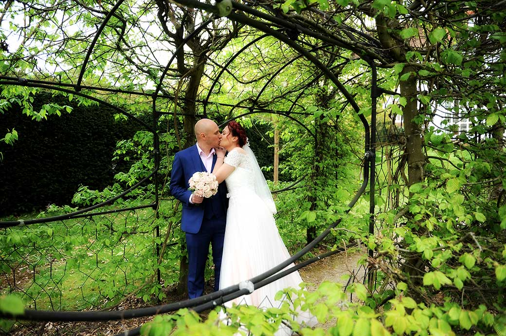 A passionate loving kiss captured at Surrey wedding venue Leatherhead Register Office as the newlyweds stroll down under the green garden arbour