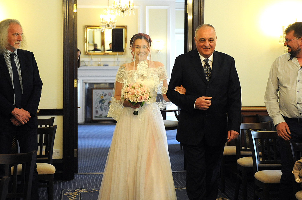 An excited Bride on the arm of her father at Surrey wedding venue Leatherhead Registry Office captured as she walks down the aisle of the State Room