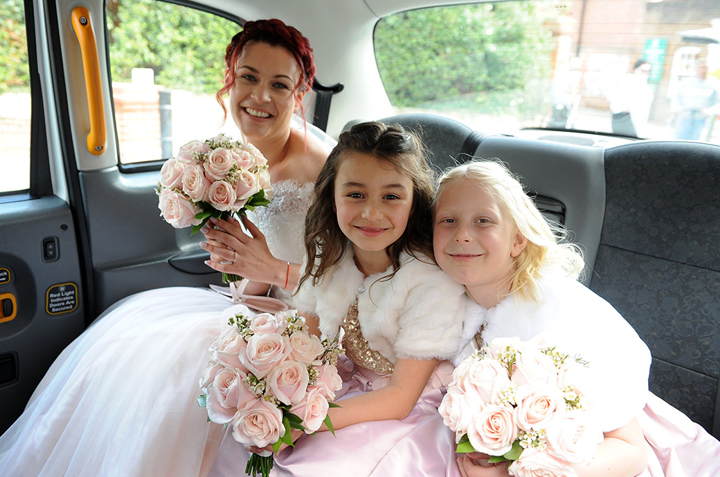 Wedding picture of a happy Bride with her two young bridesmaids posing in the back of her white cab on route for Surrey wedding venue Leatherhead Registry Office