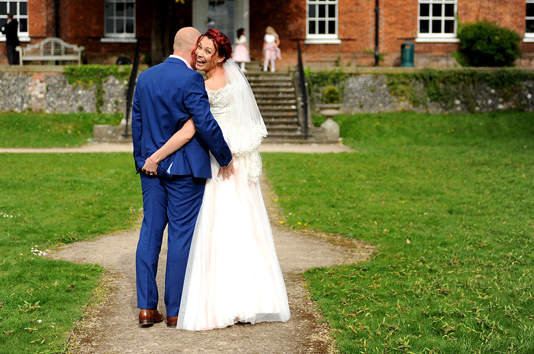 Cheeky fun moment captured in the lovely grounds of Surrey wedding venue Leatherhead Register Office as the Bride pinches her groom's bottom