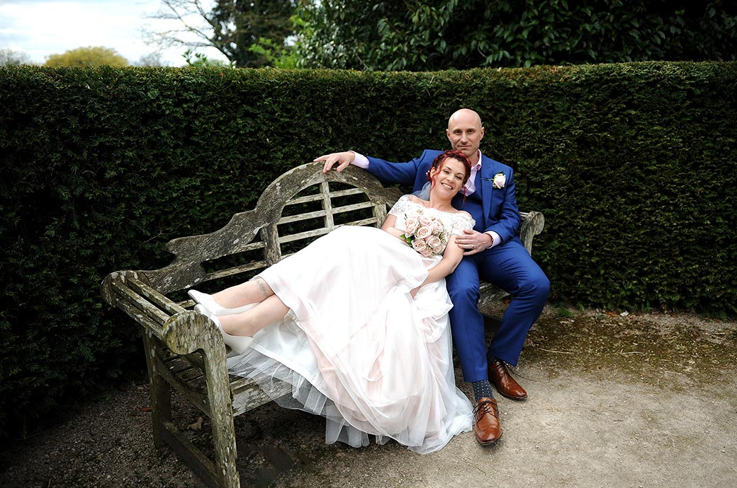 The lovely Bride relaxes as she lays her head on her husband as they take some time out on a garden bench at Surrey wedding venue Leatherhead Register Office