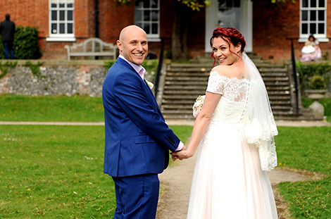 Wedding picture of a handsome smiling happy newlywed couple looking over their shoulders as they walk along the path to Leatherhead Registry Office in Surrey