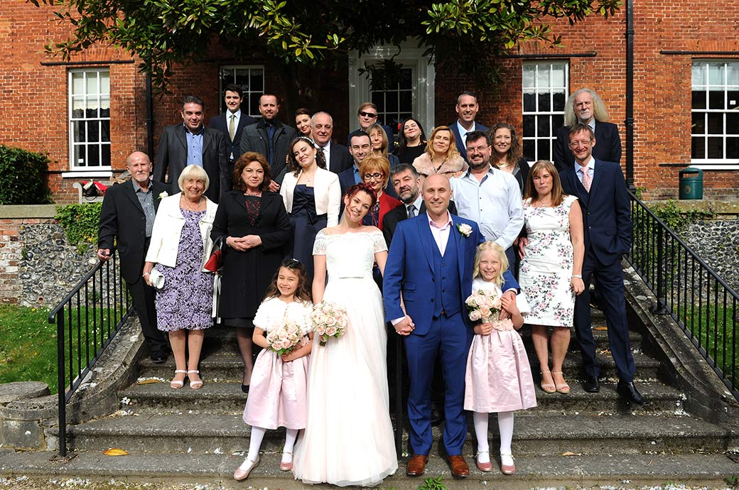All smiles for the Bride and groom with their family and friends standing on the terrace steps of Surrey venue Leatherhead Registry Office for the everyone wedding photo