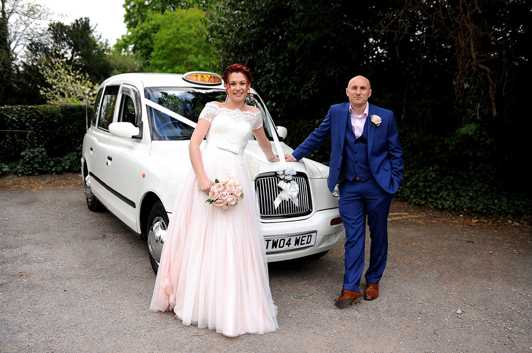 Relaxed wedding photo of the bride and groom at Surrey wedding venue Leatherhead Registry Office taken as they lean on their white cab wedding car