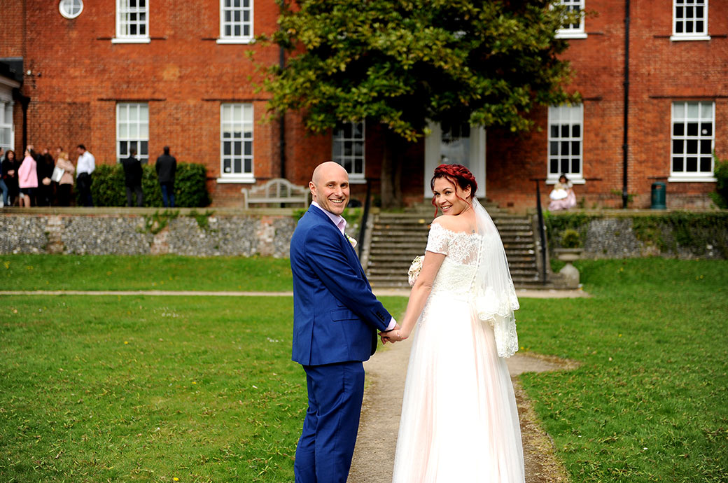 Handsome smiling and happy newlywed couple captured in this wedding photo looking over their shoulders as the walk back to Surrey wedding venue Leatherhead Registry Office