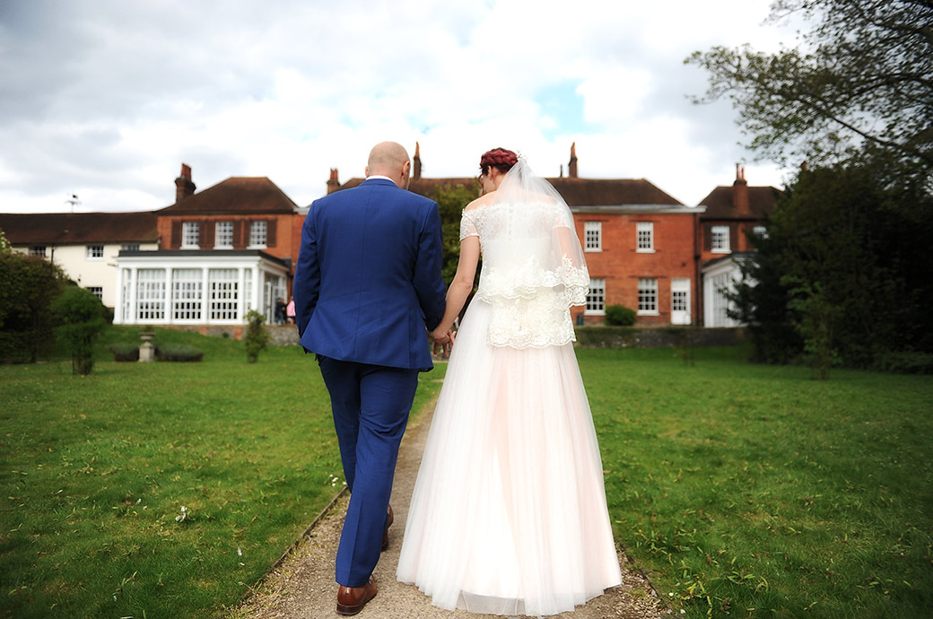 Wedding photograph taken from behind of a Bride and Groom in Surrey walking up the path through the lawn back to the Leatherhead Registry Office terrace