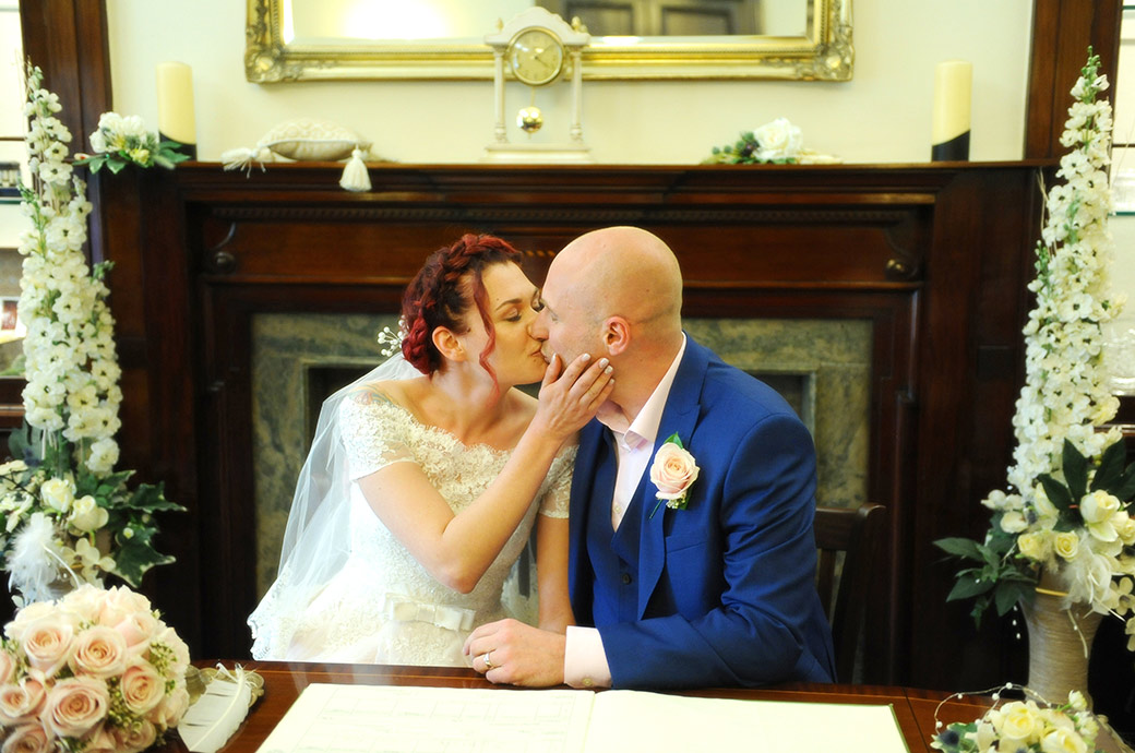 Bride and groom kiss as they sit at the registrar's table after signing the marriage register in the State Room of Leatherhead Register Office in Surrey